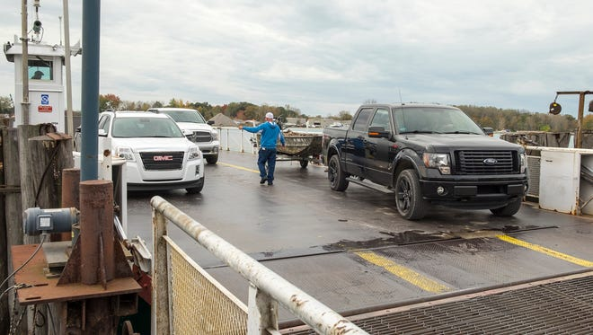 Vehicles are guided off Champion's Auto Ferry in Clay Township Thursday, Oct. 23. State Rep. Dan Lauwers introduced a bill updating oversight of the Carriers by Water Act, which would make it easier for the ferry to adjust its rates.
