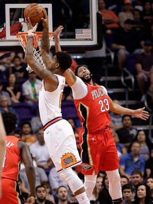 Phoenix Suns forward Marquese Chriss (0) rebounds over New Orleans Pelicans forward Anthony Davis (23) during the first half of an NBA basketball game Friday, April 6, 2018, in Phoenix. (AP Photo/Matt York)