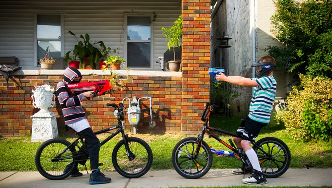 Ozzy McMasters, 11, left, and Clarence Bates, 13, both of Evansville, point toy guns at each other while waiting for other neighborhood children to join in a game of cops and robbers on W. Missouri Street in Evansville, Tuesday, Oct. 4, 2016