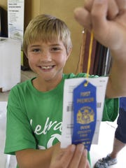 Isaac Rouer receives a ribbon for his knowledge and
