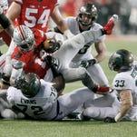 Michigan State's Craig Evans, left, and Jon Reschke drag down Ohio State quarterback J.T. Barrett at the line of scrimmage in the third quarter on Saturday in Columbus, Ohio.