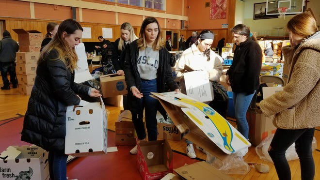 Mount Saint Mary College students help sort hundreds of pounds of food on Feb. 21, to be distributed to those in need through Newburgh's St. Mary's Church.