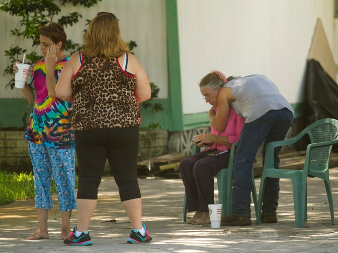 Tammy Rawson, right, is comforted at the scene of a