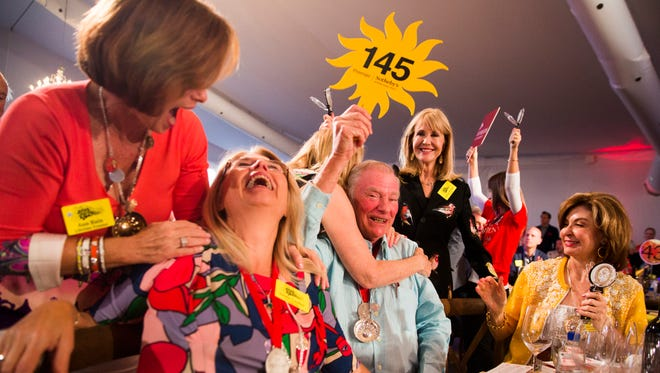 "Wayne Laufer, center, celebrates with the rest of his table after winning the bid on lot 53 for $450,000 during the 2017 ""Bright Sunshiny Day"" Auction at the Naples Winter Wine Festival on Saturday, Jan. 28,  2017, at the The Ritz-Carlton Golf Resort in North Naples. Lot 53, ""Southern State of Mind,"" includes a private performance by Darius Rucker."