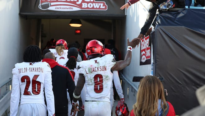U of L's Lamar Jackson (8) greets fans following their loss against Mississippi State during the TaxSlayer Bowl in Jacksonville. Dec. 30, 2017