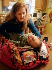Cori Salchert, who fosters sick children, gently places