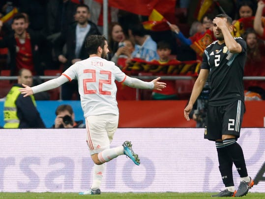 Spain's Isco Alarcon, left, celebrates scoring while Argentina's Gabriel Mercado, right, grabs his head during the international friendly soccer match between Spain and Argentina at the Wanda Metropolitano stadium in Madrid, Spain, Tuesday, March 27, 2018. (AP Photo/Francisco Seco)