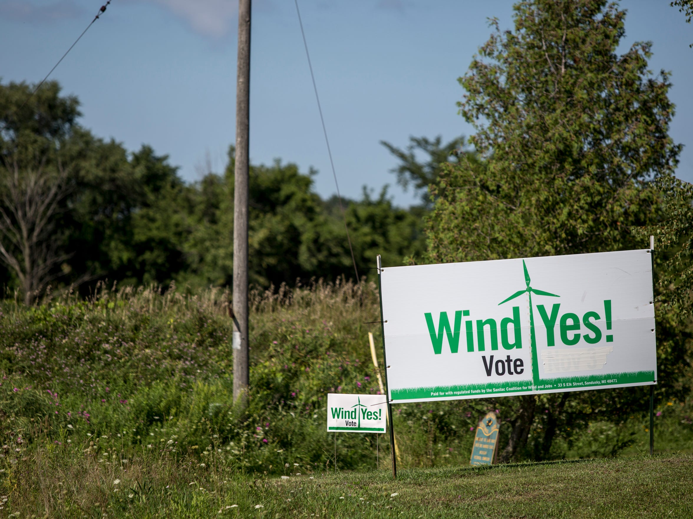 A sign is posed in support of wind turbines Thursday, August 18, 2016 in Marion Township.
