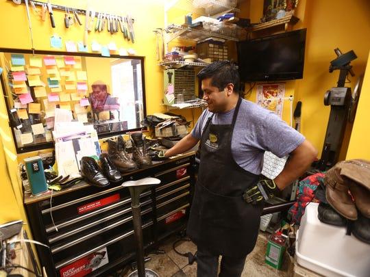 Refugio Contreras, owner of C&F Shoe Repair looks at