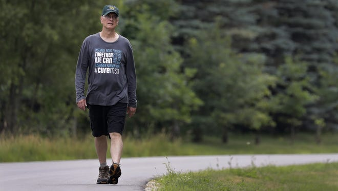 John Ewen walks in his neighborhood Thursday, which would have been his daughter Barbara's 42nd birthday. Ewen will walk across Ireland later this month to raise awareness of a genetic disease that led to his daughter's death.