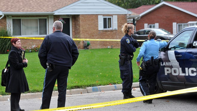 Lansing police wait for the crime scene unit at the site of a probable hit and run fatal accident on Lansing's Southside Sunday, October 5, 2014.