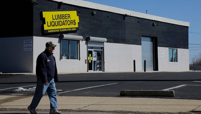 In this March 12, 2015 file photo, a man walks past a Lumber Liquidators store in Philadelphia.