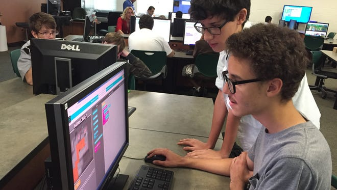 Zeke Mejiasi, 15, works through a coding problem with the help of Dubar High School classmate Leo Ruiz, 15. The two participated in Hour of Code Wednesday at the school.