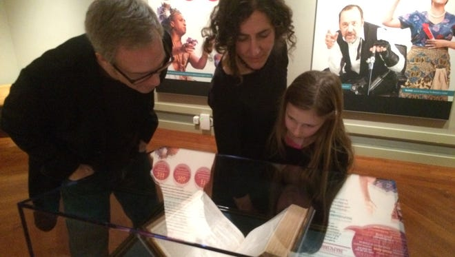 Timothy Billings, professor of English at Middlebury College; Rebekah Irwin, the college's director of special collections; and her daughter, Ruby Harrison, look at William Shakespeare's first folio Saturday at the Middlebury College Museum of Art.