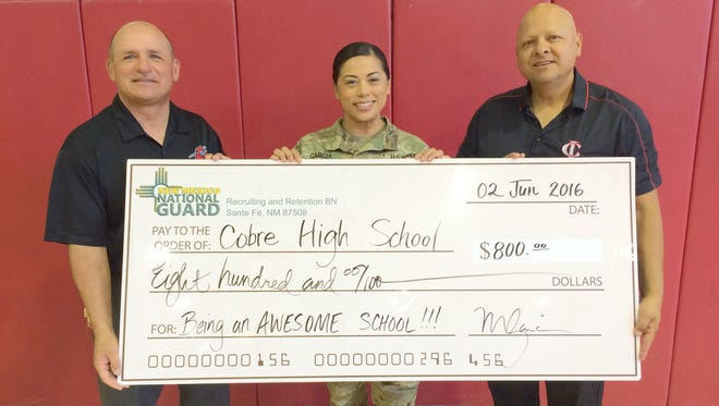 From left, Cobre High principal Frank Quarrel, NM Army National Guard SSG Melissa Garcia, and athletic director Pat Abalos pose with a donation receieved.