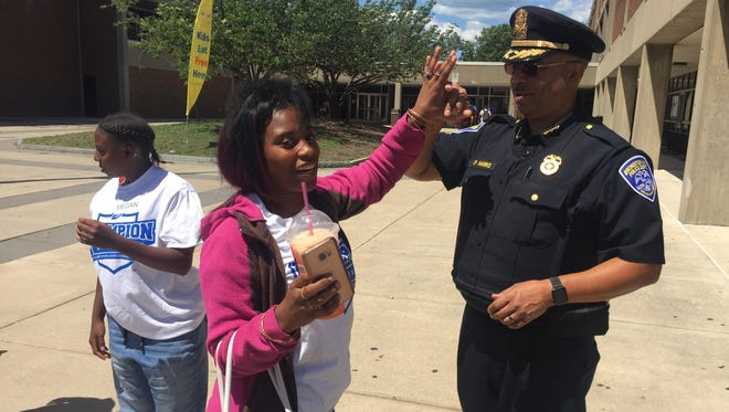 """Rochester Police Department Deputy Chief Wayne Harris greets a member of the Champion Academy during a two-week educational summer program. The academy, founded by former NFL tight end and Rochester native Roland Williams, hosted a """"Stop the Violence'' day."""