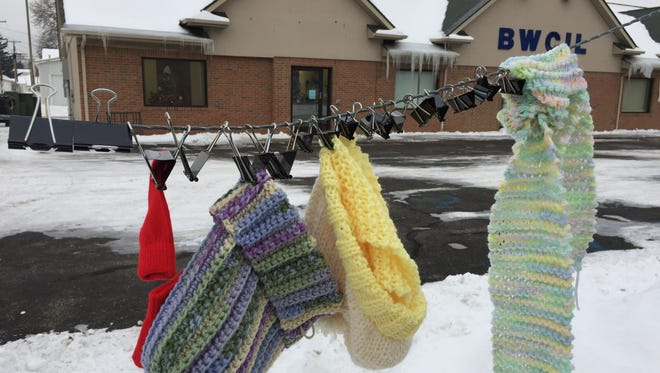 Knitted items hang on a clothesline at the Blue Water Center for Independent Living.