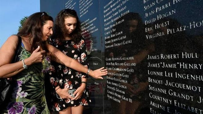 Murielle Coste, of Tucson, Arizona, with her daughter, Sedona, by her side, touches the name of her father, Francis Gaston Gasq, on the memorial wall during the 20th anniversary of the TWA Flight 800 plane crash at Smith Point County Park on Sunday, July 17, 2016, in Shirley, New York. Families and friends of some of the 230 people killed when a Paris-bound TWA flight 800 jet exploded in the sky off the Long Island coast commemorated the 20th anniversary of the crash that took place on July 17, 1996.