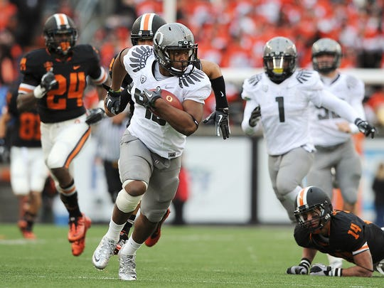 Oregon's Michael Clay sprints away from Oregon State's Jordan Poyer (14) and Ryan McCants 64-yard rush on during a fake punt in the first half of an NCAA college football game, Saturday, Dec. 4, 2010. (AP Photo/Albany Democrat-Herald, Mark Ylen)