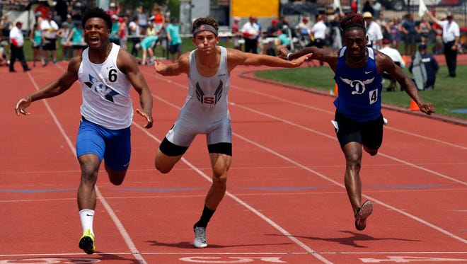 Sheridan's Jacob Rhodes crosses the finish line with CVCA's Tre Tucker, left, and Dunbar's Jalani Allen, right, during the boys 100 meter dash Saturday, June 2, 2018, during the state track and field championship at Jesse Owens Memorial Stadium in Columbus.