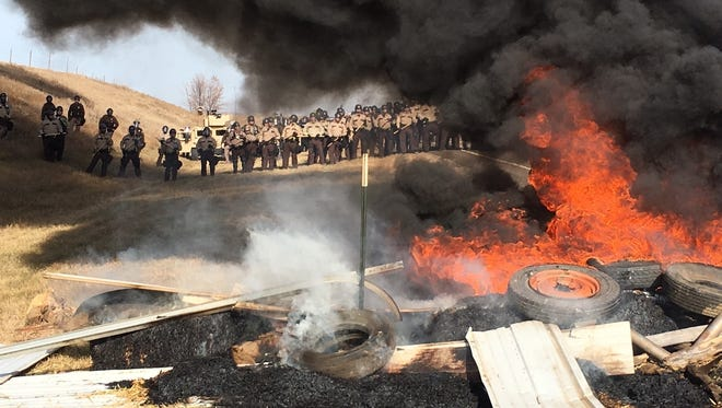 Tires burn as armed soldiers and law enforcement officers stand in formation on Oct. 27, 2016, to force Dakota Access pipeline protesters off private land in Morton County, North Dakota. On the same day seven defendants celebrated acquittal in Portland, Oregon, for their armed takeover of a federal wildlife refuge in Oregon, nearly 150 protesters camped out in North Dakota to protest an oil pipeline were arrested.