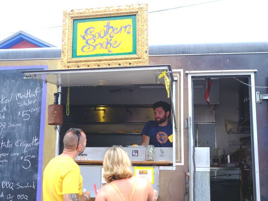 Brian Stefan, owner of Southern Smoke barbecue, serves customers at the 2015 Vermont Cider Classic on July 25, 2015, at ArtsRiot in Burlington.
