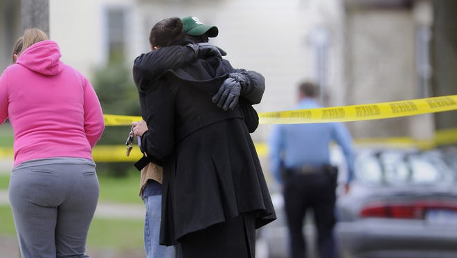 People console each other on Fenton St. in Lansing Thursday 4/23/2015.  Police are investigating an incident as a homicide.