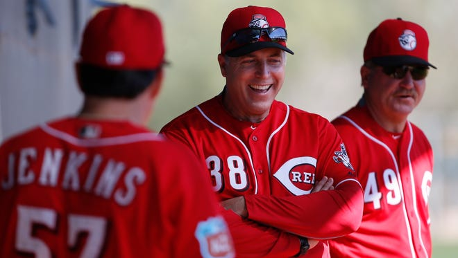 Cincinnati Reds manager Bryan Price (38), center, smiles along with bullpen coach Mack Jenkins (57), left, and pitching coach Mark Riggins (49), during a bullpen session at Cincinnati Reds spring training, Monday, Feb. 22, 2016, in Goodyear, Arizona.