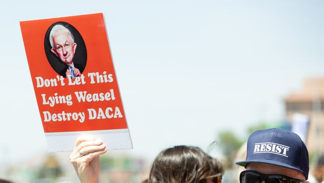 "Sam Peters, of Las Cruces, holds a sign that reads ""Don't let this lying weasel distroy DACA,"" on Wedensday, April 11, 2018, while protesting Jeff Sessions arrival to Las Cruces New Mexico."