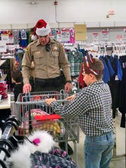 Deputy Steve Strang with the San Juan County Sheriff's Office helps his shopping partner during the Shop With Your Cops event on Dec. 12 at Kmart in Farmingotn.