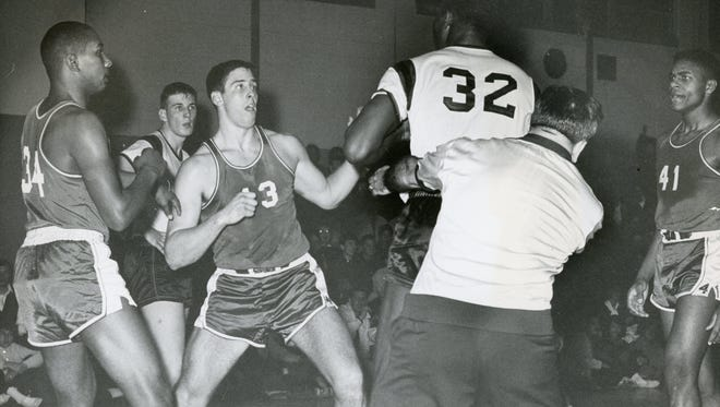 Neptune's Jim Bell (32) is restrained by referee Joe Palaia in an altercation with Manasquan's Jim Grasdorf (43) during a game on Jan. 22, 1963 at Neptune High School. Looking on are Manasquan's Ronnie Scavella (left) and Reggie Lyons (right).