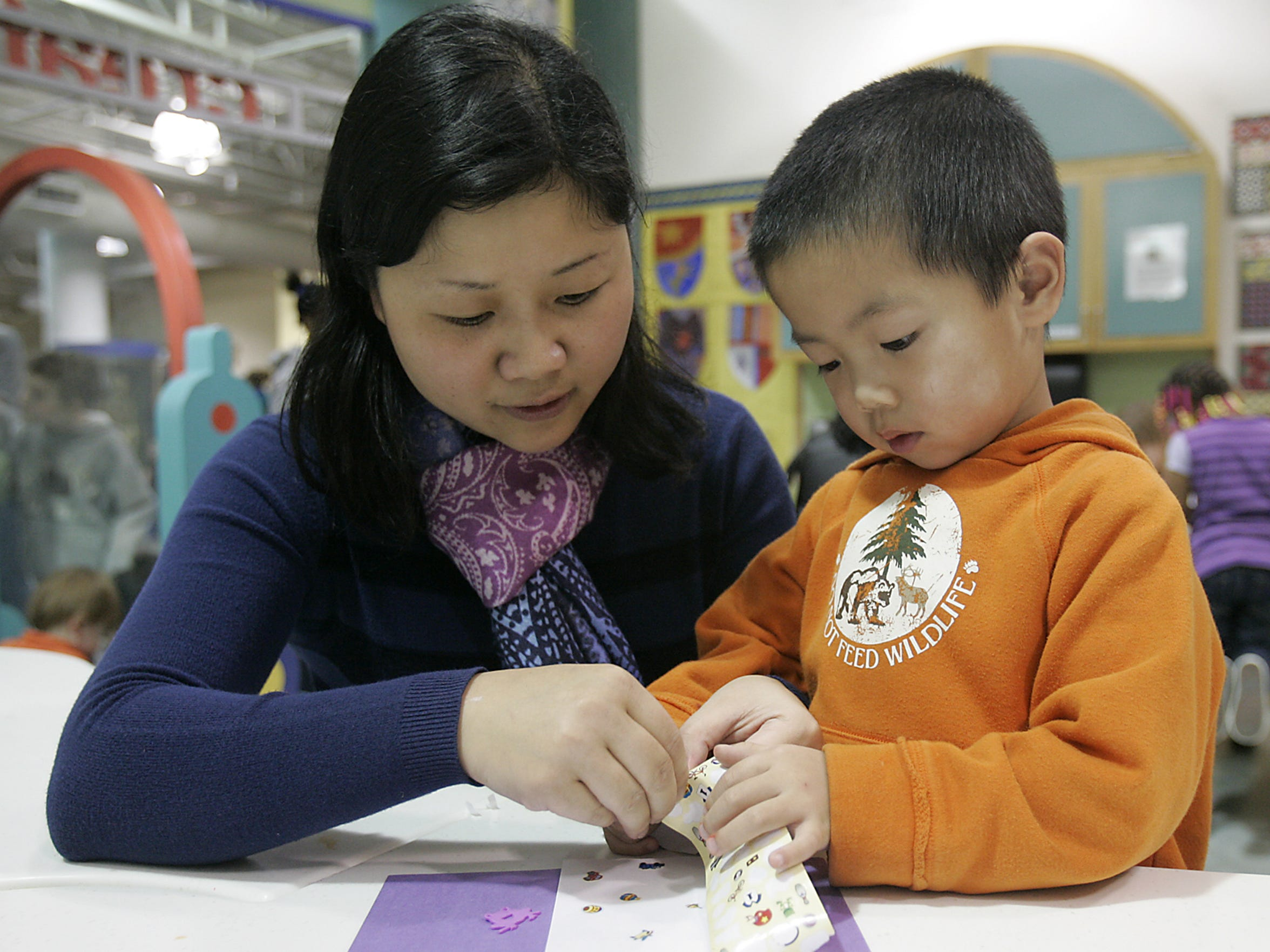 Li Liu Chen works with her son William to make a thank you card to the troops as part of the MLK Day activities held at the Discovery Center.
