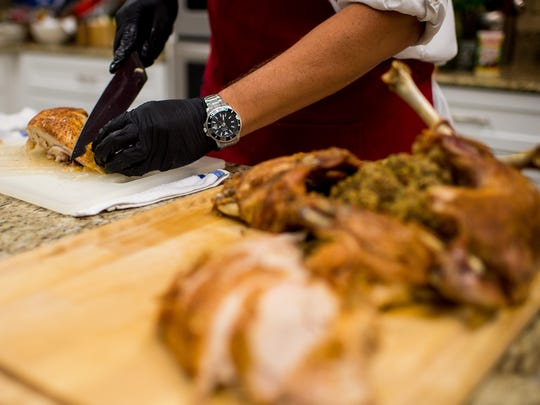 Jude Tauzin, corporate chef for Tony Chachere's Creole Foods, slices freshly roasted chicken breasts on a cutting board in Opelousas, La., Wednesday, Nov. 4, 2015.