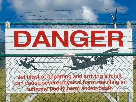 A Danger sign warns people not to stand being departing