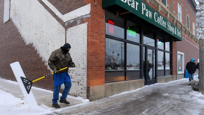 Steve Stiles, owner Bear Paw Coffee Shop and Deli in Big Sandy, shovels the sidewalks as snow continues to fall Thursday afternoon. Negative temperatures are expected throughout northcentral Montana, with bitter cold weather settling in Friday and Saturday.