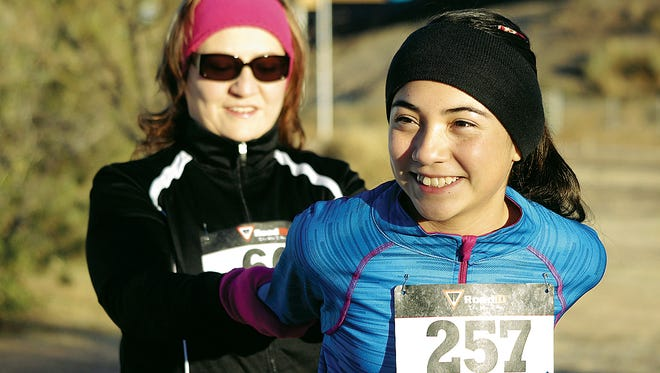 Kaitlyn Garcia gets a good stretch from her mother, Lupe Rincon Garcia, prior to 2013 Ultimate Fitness Turkey Trot at Voiers' Park.