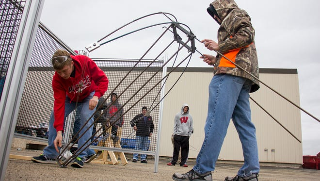 Mayville High School students Weston Wiese, (left), and Andrew Nothem get their catapult ready for launch at Moraine Park Technical College's recent Distance Challenge. The team took second place with a throw of 192 feet.