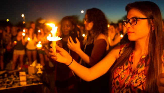 Salina Lopez holds a candle during a vigil for Jason Josaphat on Wednesday, June 15, 2016, at Skyline Park in Mesa. Josaphat, a 2014 graduate of Skyline High School in Mesa, was killed in Sunday morning's terror attack at the Pulse nightclub in Orlando, Florida.