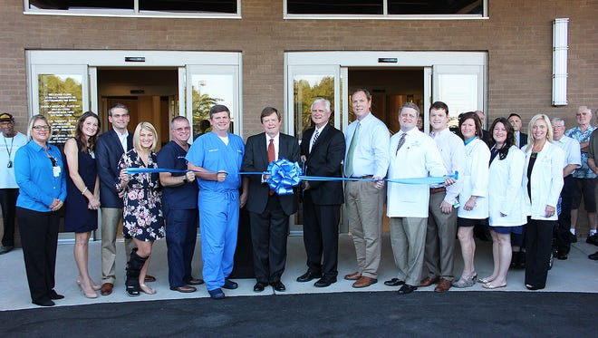 Clinic administration and providers gather to cut the ribbon for Hattiesburg Clinic's new multi-practice medical facility, Hattiesburg Clinic – Bellevue. Pictured from left are Bellevue Physical Therapy providers – Tiffany Smith, PTA; Brandie Bennett, PT, DPT; Jeremy Bennett, PT, DPT, CSCS; Eye Associates providers – Casey Wells, CNP; Curtis Shaffer, OD; Christopher Cooley, MD; Tommy Thornton (center), Hattiesburg Clinic executive director; and Bellevue Family Medicine providers – Jack Hudson, MD; Lane Pitts, MD; Brett Robbins, MD; Allen Martin, DO; Lisa Bailey, CNP; Breanne Leathers, CNP; Jennifer Pattie, CNP.