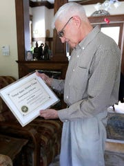 Scott Rodman looks at his certificate that allows him