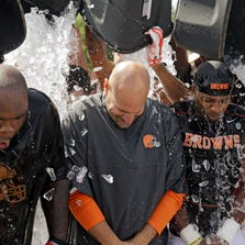 Cleveland Browns nose tackle Phil Taylor, left, head coach Mike Pettine, center, and cornerback Justin Gilbert get ice dumped over them after practice at NFL football training camp in Berea, Ohio. As of Aug. 21, the ALS Association had raised $41.8 million dollars.