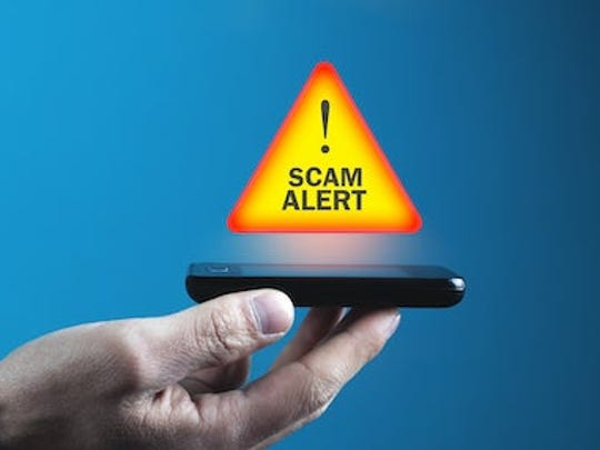 Hand holding phone up, with a Scam Alert caution icon floating above the screen.