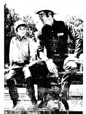 "Joe Bill Nunn and his seven-year-old son, Justin, sit in a familiar environment-a cattle pen. Nunn, a young Luna County rancher, has been selected by the BorderBelles for their annual ""Father of the Year"" award. He actively supports the BorderBelles in beef promotion campaigns, and is the husband of a BorderBelle, Lauren, who also is president-elect of the New Mexico CowBelles. (Photo by Deborah Walker)"