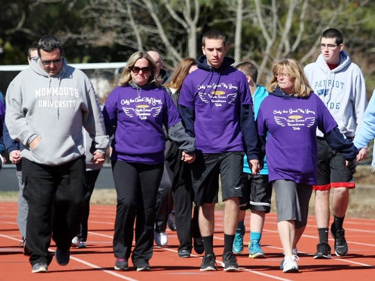 "From left: Mike Surace, wife Diane and son Kevin walk the first lap at the first annual ""Only The Good Fly Young"" Nicole Elizabeth Surace Remembrance Walk on April 6, 2014. The fourth annual Only the Good Fly Young Nicole Elizabeth Surace Remembrance Walk to benefit the scholarship fund in her name will be held April 2 at Monmouth University."