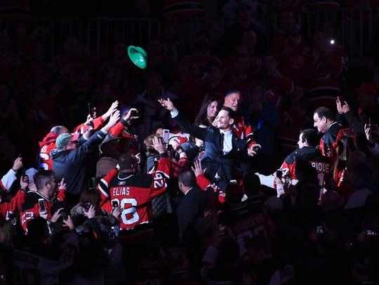 Patrik Elias throws a hat as he walks through the crowd
