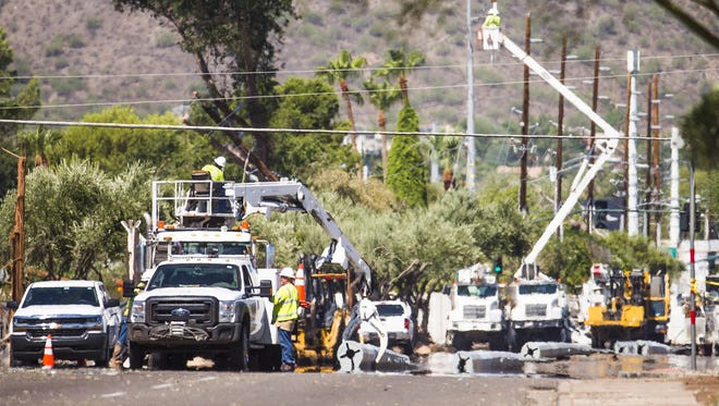 APS employees try to repair downed power lines on Shea Blvd. and 40th Street in Phoenix on Aug. 4, 2017.
