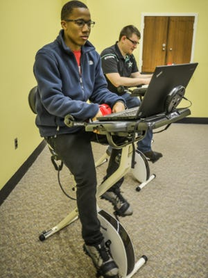 Troy University students Jalen Bivens and William McCarthy use exercise study desks inside the library.