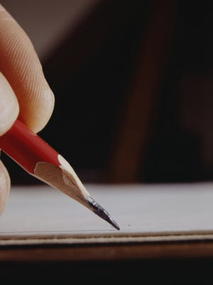 Man writing with pencil, close-up of hand