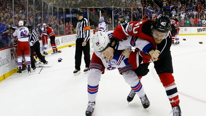 Devils' Blake Coleman (40) and Rangers left wing Jimmy Vesey (26) fight each other while teammates engage in their own fights during the second period of Tuesday night's game.