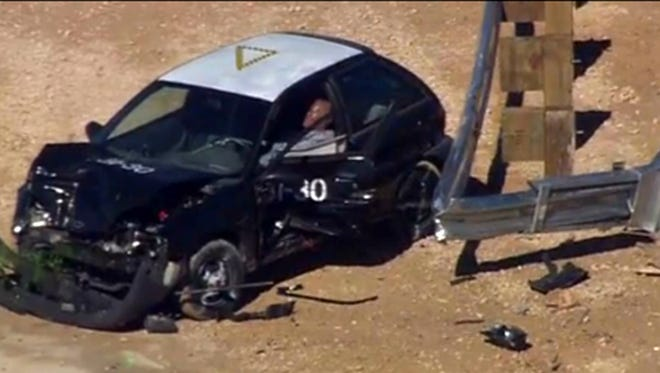 A small car sits mangled after a crash test for the Trinity ET Plus guardrail end terminal